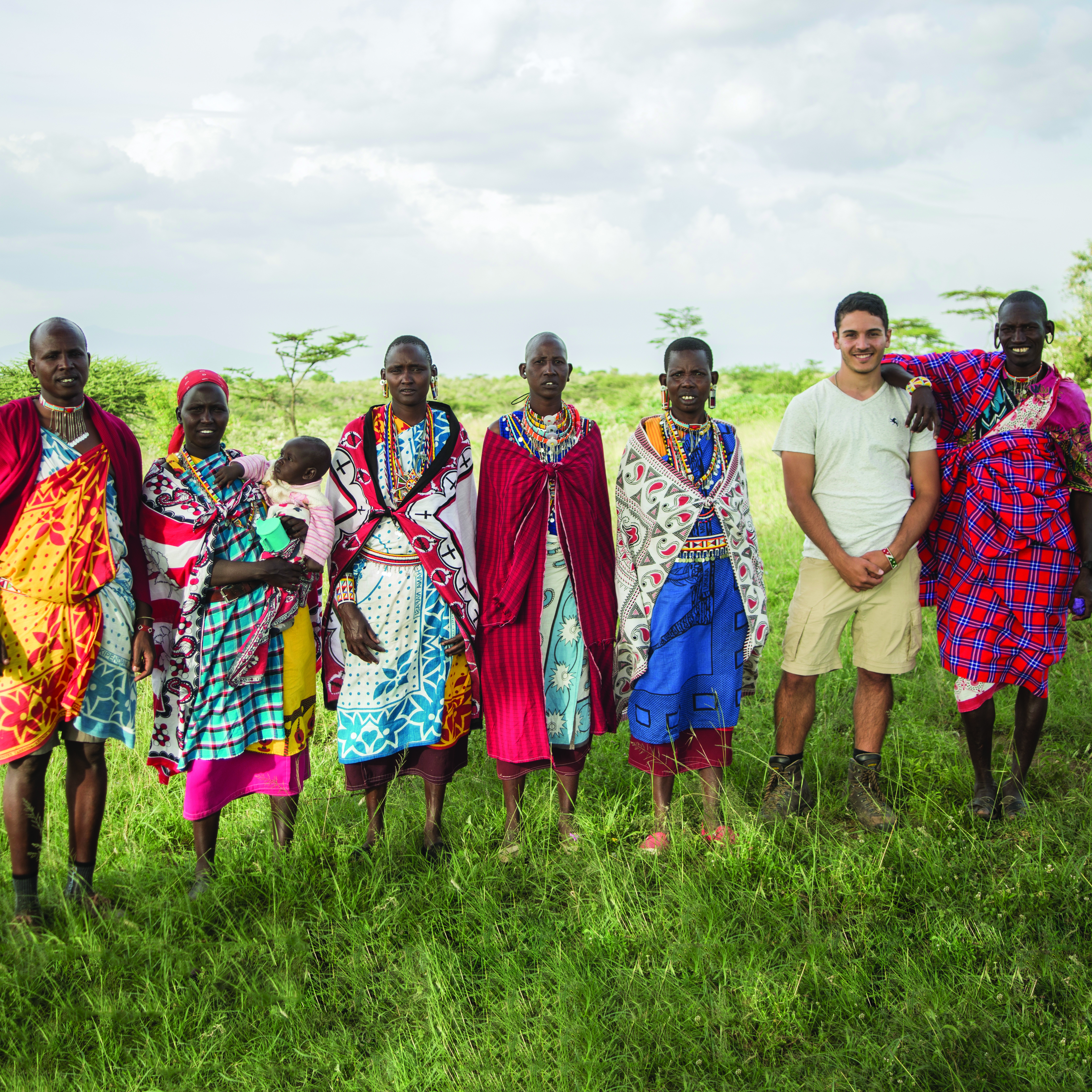 student standing with group of people in Africa from study abroad/volunteer experience