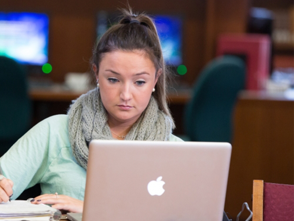 a girl writing while looking at a laptop screen