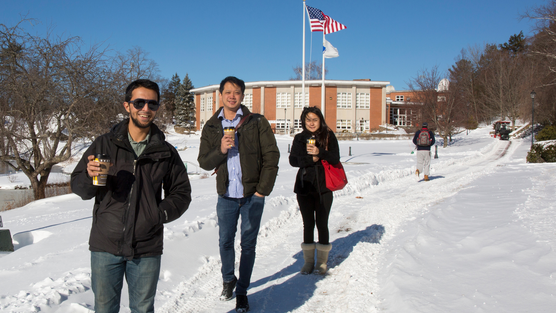 Three Endicott students walking from the academic center in the snow